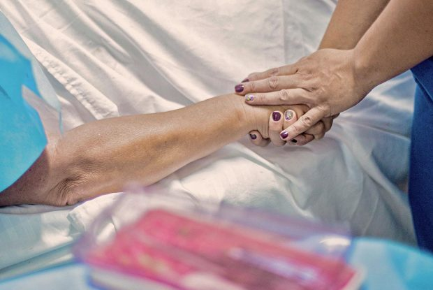 Healthcare Risk Management Nurse Holding Patient Hand
